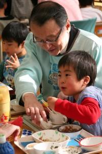 幼児と給食をとる中川文部科学大臣