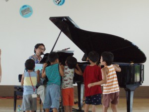 ピアノの周りで演奏を楽しむ子どもたち