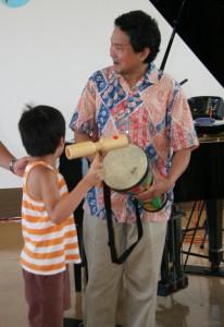 打楽器を叩いて演奏に参加する子ども