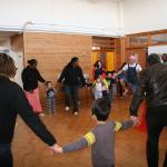 幼児たちと一つの輪になって踊る研修員たち