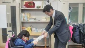 新津次長に報告書を手渡す高橋葵さん